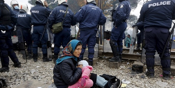 A refugee breastfeeds her baby behind a Greek police cordon as she waits to cross the Greek-Macedonian border near the village of Idomeni, Greece December 4, 2015. REUTERS/Yannis BehrakisTEMPLATE OUT      TPX IMAGES OF THE DAY