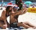 Beachgoers Tara O'Sullivan and Tomek Juszczyk pose for selfie photos as they spend Christmas Day on Sydney's Bondi Beach, Sunday, Dec. 25, 2016. (Dan Himbrechts/AAP Image via AP)